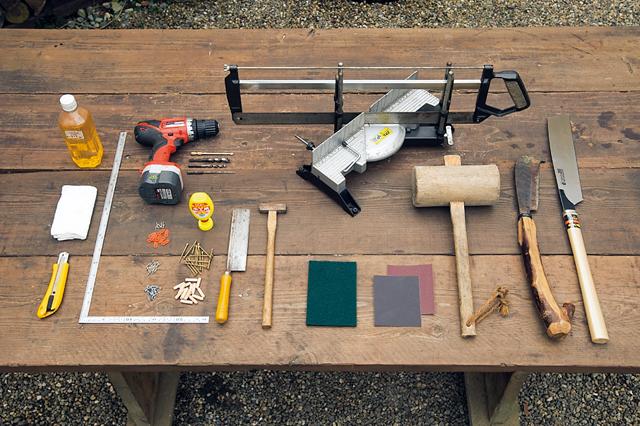 右から丸太整形用ののこぎり、鉈 なた 、木 き 槌 づち 。木材 カット用のソーガイド、サンドペーパー(2種)、 ビニールたわし、金槌、小さめののこぎり(ダ※ ボ切断用)、電動ドリル(刃は細太4種類)、木 工用接着剤、木ねじ、ダボ、トンボ(留め具)、釘、 指さし金がね、クルミ油、ぼろ布、カッター。