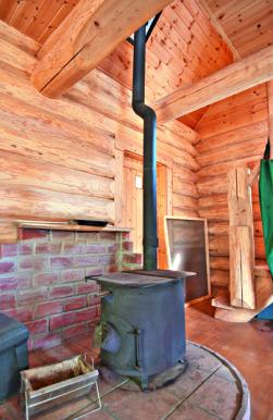 本宅は5.4×5.4mの床面積を持つ2 階建て。「ここは標高が300mあって 夏は木々に覆われるから、冷房は全く いらない。冬は囲炉裏と薪ストーブが 熱源。裏山の雑木で完全に自給できる」