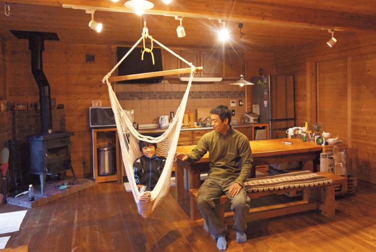 手作りの大テーブルとハンモックが据えられたリビング。 仕切りが少なく、開放感あふれる太田家の憩いの場。