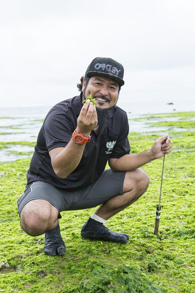 海人歴10年の赤嶺さんがアーサを採ってくれた。手に持っているのはタコを捕る棒。ファンキーな見た目だが海を愛する心は深い。