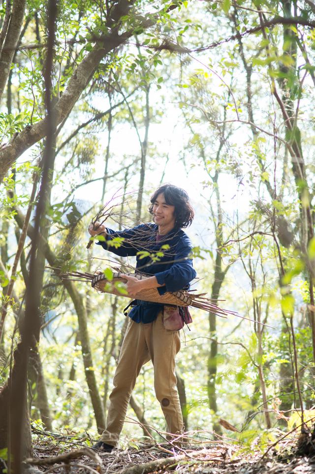 森の中から、イメージ通りの枝を探してまわるテンダーさん。「地面におちているものより立ち枯れの方が、含水率が低くてよく燃えますよ」