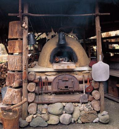木材で組んだ土台の上に、土と砂 とわら(断熱効果を高めて熱効率を 上げられる)を混ぜて作った土窯を 設置。仲間と数人がかりで4日間か けて完成させたもの。周囲には火鋏 や火吹き竹など土窯グッズが並ぶ。