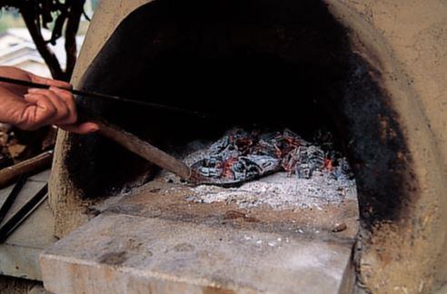 土窯を温めるため、朝6時から火 入れ。3時間ほど薪を燃やしたら、 火を取り出して200度Cまで冷ます。