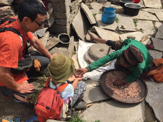 お豆を石臼で挽いて粉にしていた女性。お豆をもらう子ども。