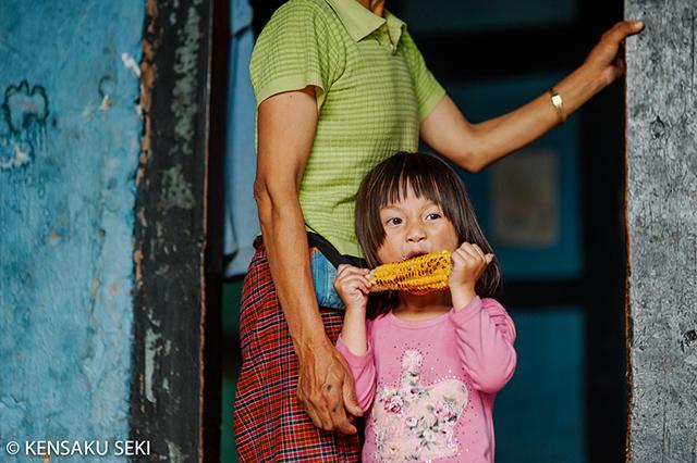 トウモロコシを貪る少女キンレー、今年(2016年)7歳。無邪気で明るい少女。