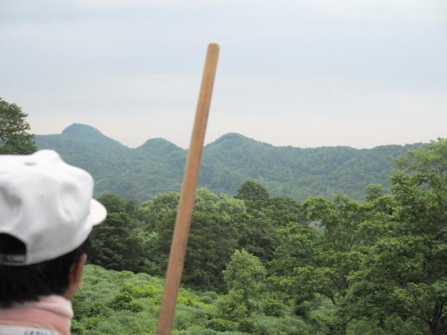 ガイドの山本さん。棒が指しているあたりが粟峠(後述)、その左が大網峠、右が鳥越峠だそう。