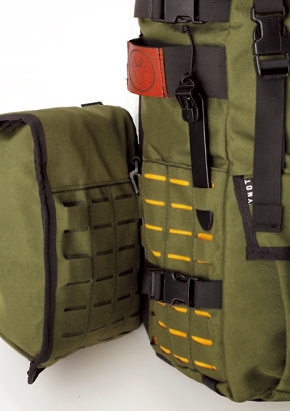 サイドポケットの取り付け には、ミリタリー仕様のペグ のようなバックルを使う。本体側とポケット側のスリットを縫うように交互に通すから、ガッチリ装着できる。