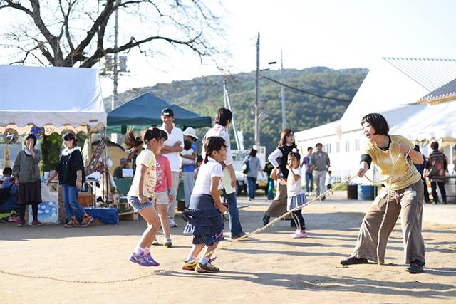 里山を望む校庭で、都会の人も、田舎の人も、大人も、子どもも一緒になって遊ぶ