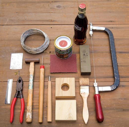 右から糸鋸、ボトル、ガラス用砥石、耐水性サンドペー パー、オイルステイン、刷毛、75㎜四方の板2枚(1枚 は中央にボトルの口に合わせて穴をあける)、彫刻刀、 錐きり、金槌、ステンレスワイヤー、トタン板、アルミシー ト(粘着付き)、ペンチ、くぎ。ほかに、ボトルカッター。