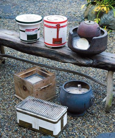 火鉢と七輪を、用途に 合わせて使い分ける 上段右からお茶用の風炉。室内や 野点でお茶を立てるときに使用。 着火練炭用七輪は長時間の暖とり に。ずっとお湯を沸かしておくと きにも便利。炭火コンロ七輪は暖 とり、煮炊きと万能選手。七輪は 下部に空気弁があるので、火力調 節が可能。下段後列は鉄火鉢とお 手製の箱火鉢。鉄製は水にも強く、 外でもOK。木製の箱火鉢は室内 の板の間などで手を温めつつ作業 するのに重宝。前列の箱七輪は料 理に限定。長四角の形状を利用し、 サンマや焼き鳥を焼くのに活躍。
