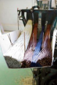 専用機械に色ごとに素材をセッ トして織り上げる花ござ。縦糸は イグサ、横糸はポリエステル由来 の糸なので、伸縮がよく丈夫。
