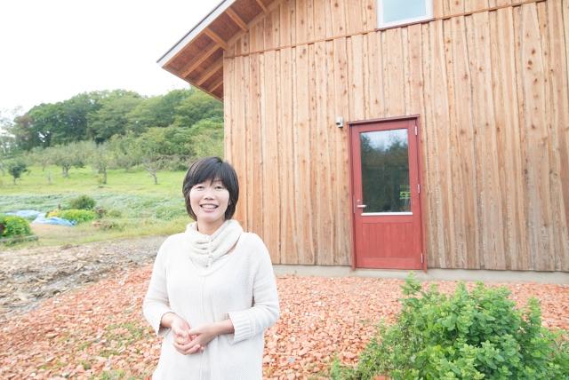 『余市エコカレッジ』の坂本純科さん。果樹 園と畑の隣に建てられた研修棟の前で。ワイ ンブドウの栽培管理やエコ建築などの実習を 年間講座で体験することができる。