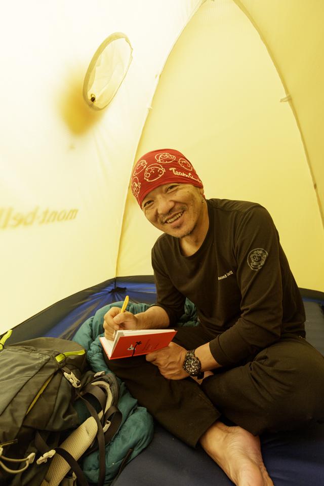 ビーパルで旅をはじめて27 年経過した、シェルパ斉藤 さん。1日の旅のシメが、 手帳への記録。テーブルが なくても、ご覧のとおり!