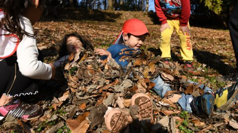 落ち葉に隠れようとする子ども達。 乱暴に作業をすると目や口に落ち葉が入ることを体感し、その後はゆっくり作業を進めていた。