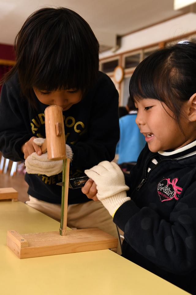 協力し合いながらまずは竹を半分に割る。 この作業を通して、この後の作業もお隣どうしで協力しあえるようになす。