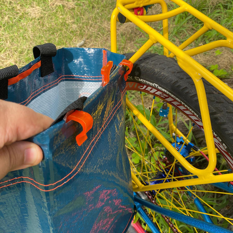 オレンジの樹脂製のフックを後ろの荷台にかければ簡易パニアバッグの完成です!